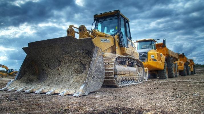 buldozer en vrachtwagens op bouwterrein