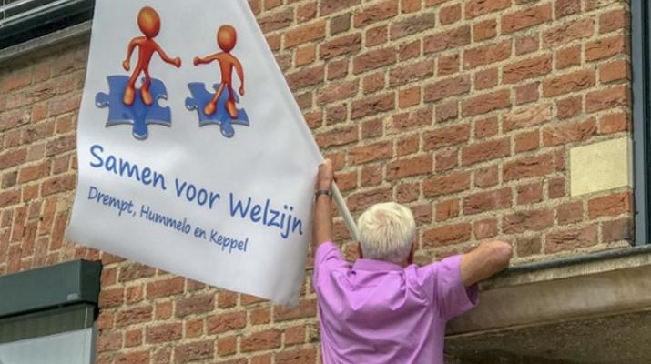 Gerard van Heusden en vlag met nieuw logo Stichting Welzijn Drempt, Hummelo en Keppel