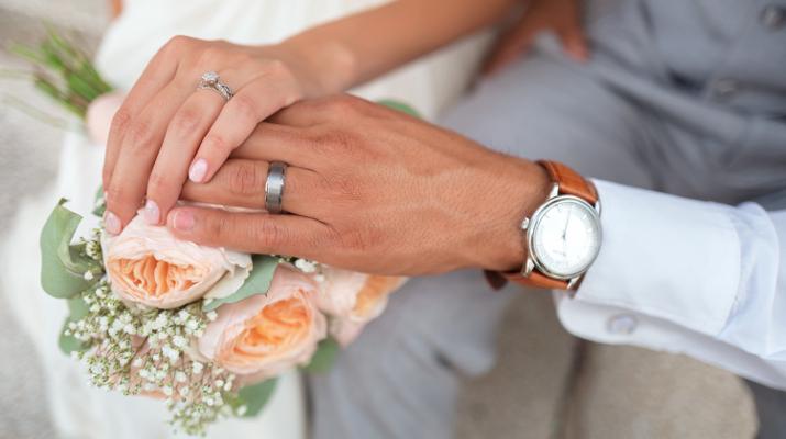 hand van bruid en bruidegom boven bruidsboeket