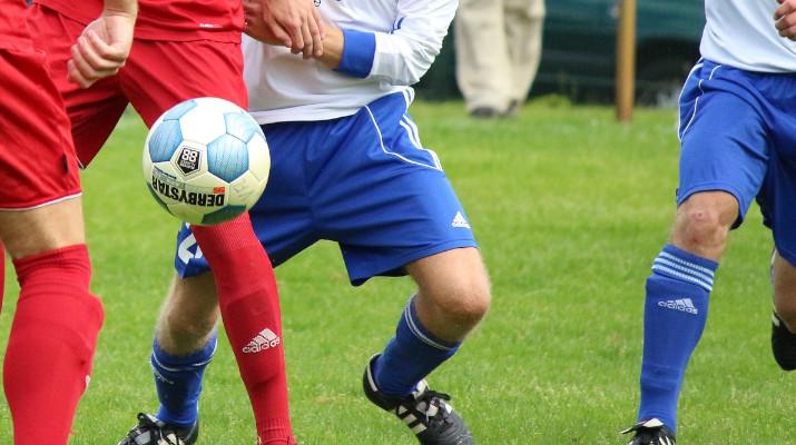 benen van voetbalspelers met bal in de lucht