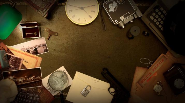 typemachine, klok, cijferslot, sleutel, loep en andere tools in het lamplicht in een donkere ruimte