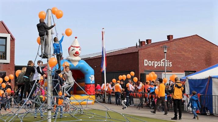 jong en oud met oranje ballonnen voor het dorpshuis op Koningsdag