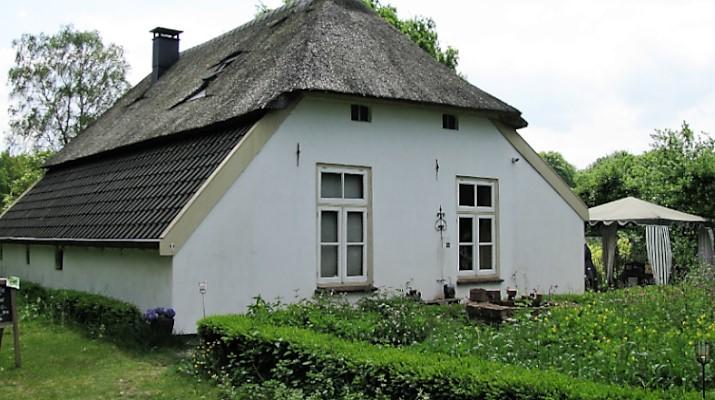 monumentaal wit boerderijtje met rieten dak met op de voorgrond groene beplanting