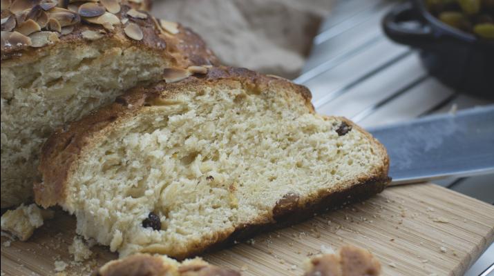 snee met mes op broodplank voor een Paasbrood