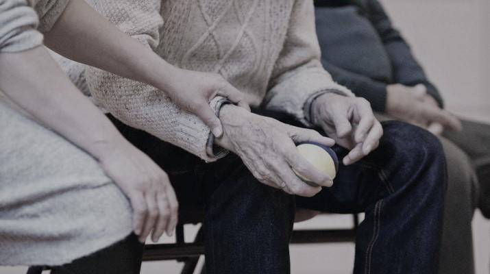 oudere man met balletje in de hand wordt bij de pols vastgehouden door jongere vrouw