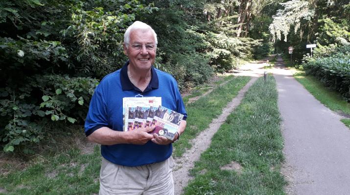 vrolijk lachende man op bospad met informatieboekjes in de handen