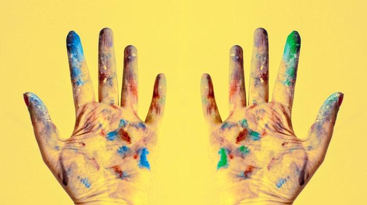 oude handen onder de verf tegen een gele achtergrond