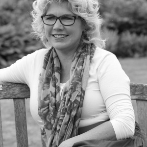 vrouw met bril schuin zittend op een tuinbankje