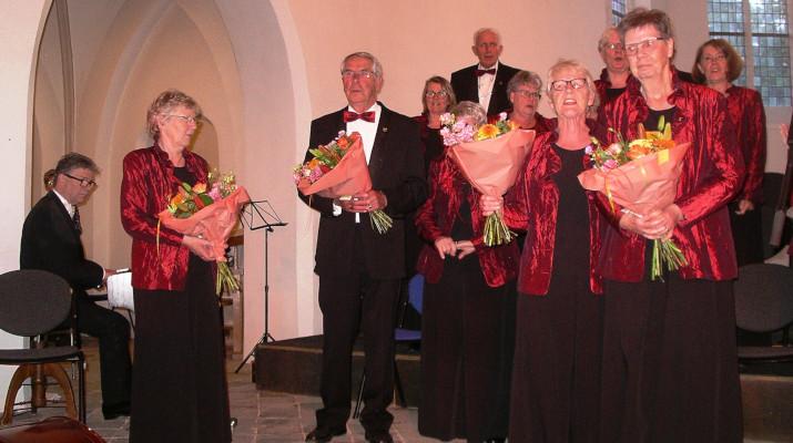 pianist en koorleden in rode en zwarte kleding met boeketten in hun handen