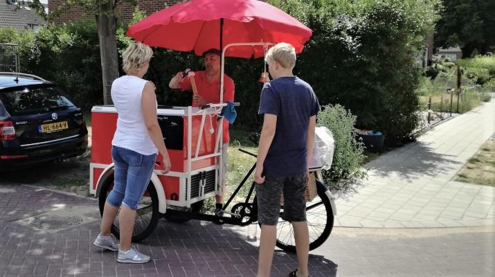 ijskar met fiets en rode parasol, ijscoman en klanten