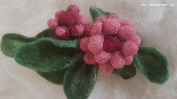 rosekleurige bloemen met groene blaadjes van wolvilt
