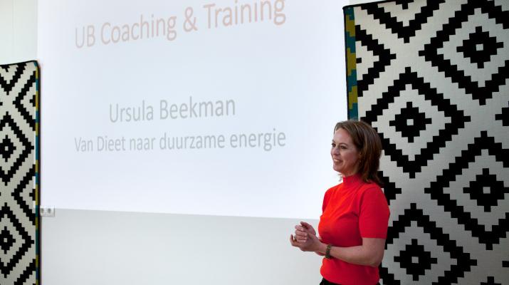 vrouw in rood shirt voor projectiescherm met tekst