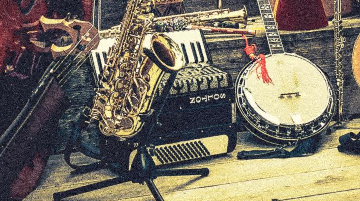muziekinstrumenten op een rij, waaronder saxofoon, accordeon, banjo, contrabas en klarinet
