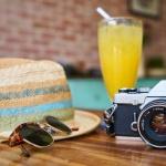 zonnehoed, zonnebril, cocktail en fotocamera