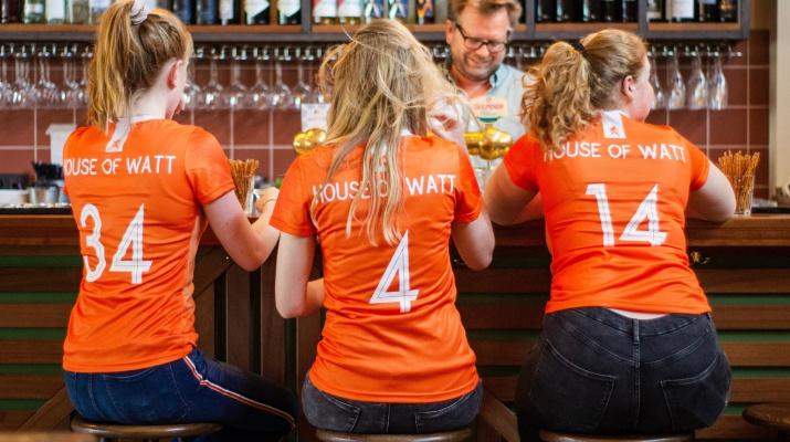 vrouwen in oranje shirt op kruk in pub