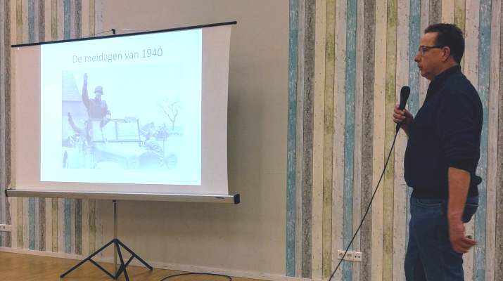 man met microfoon naast projectiescherm