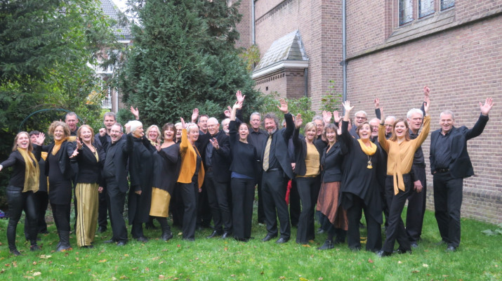 gemengd koor poseert enthousiast voor kerk