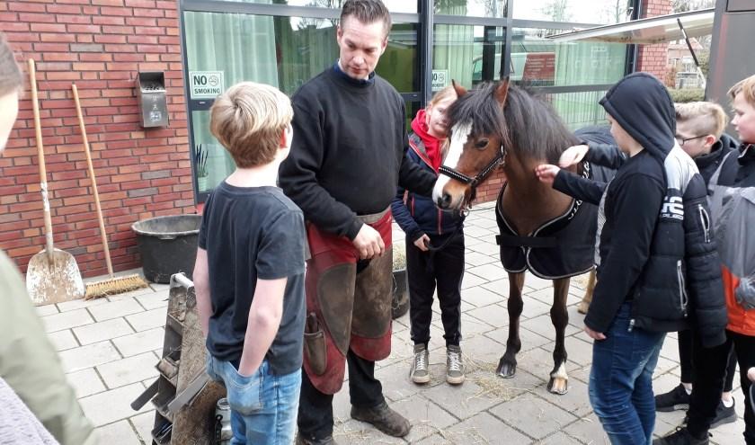 hoefsmid met paard en kinderen