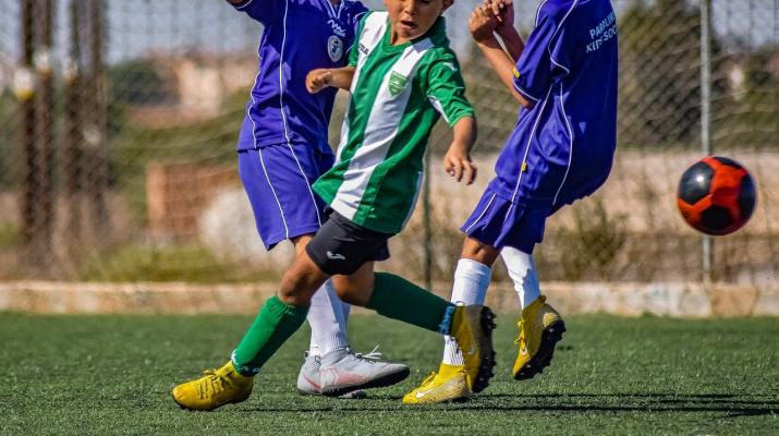 drie jongens voetballen