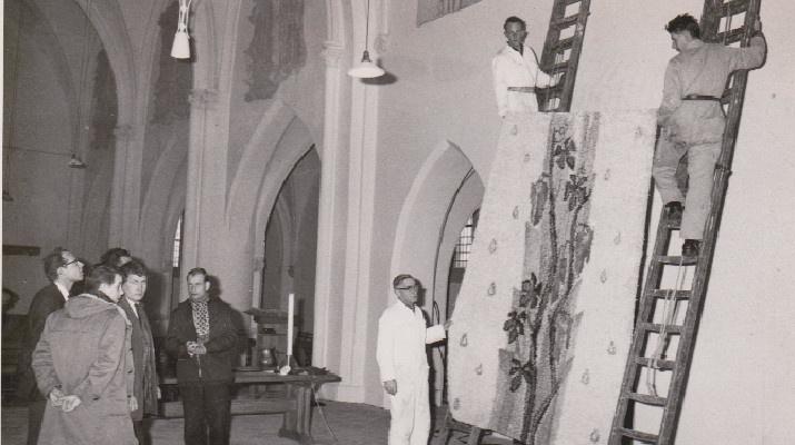 mannen hangen wandkleed op in de kerk onder toeziend oog