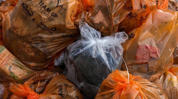 transparante vuilniszak tussen oranje vuilniszakken