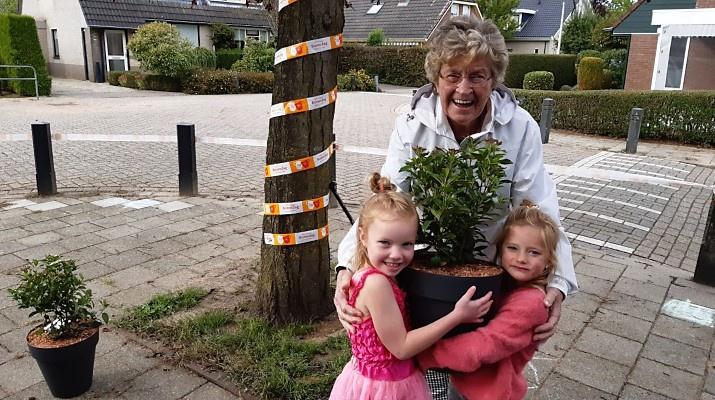 oudere vrouw met twee kleine meisjes houden samen een plant vast