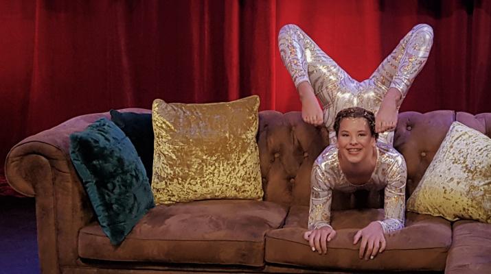 meisje in acrobatische houding op zitbank met kussens