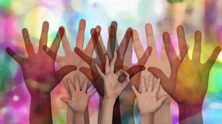 meerdere handen in kleurige omgeving