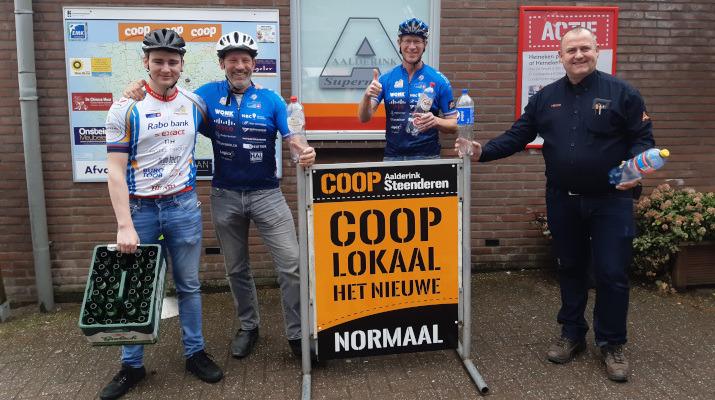 4 mannen waarvan 3 wielrenners bij supermarkt
