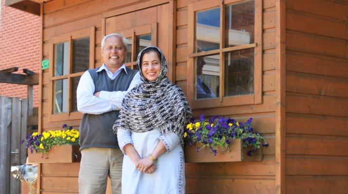 Pakistaanse man en vrouw voor tuinhuis met violen