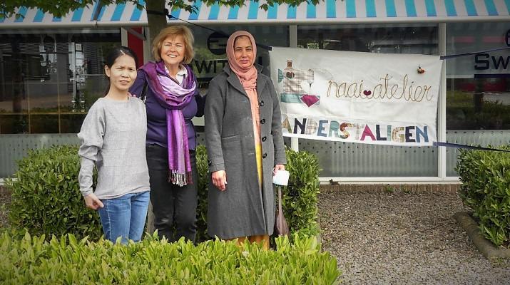 3 vrouwen naast spandoek met tekst Naaiatelier Anderstaligen