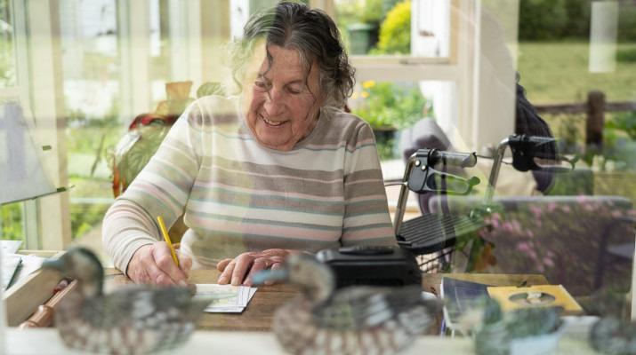 oudere vrouw knutselt aan tafel
