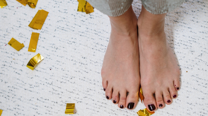 blote vrouwenvoeten tussen goudkleurige confetti
