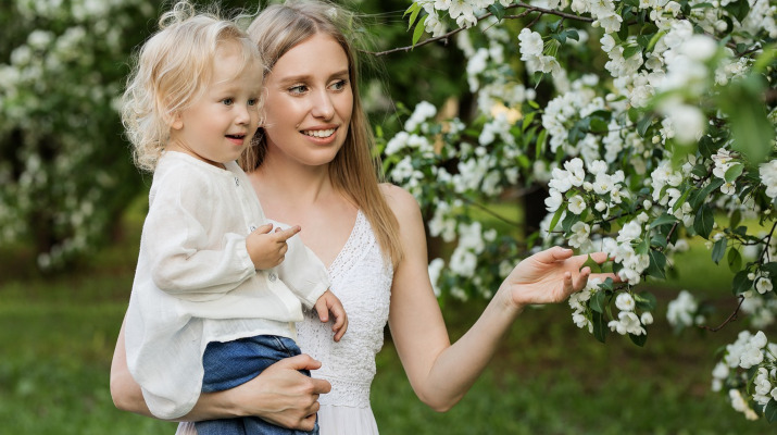 vrouw met meisje op arm bij bloeiende boom